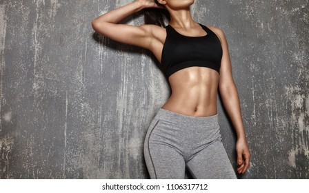 Beautiful woman posing in sport clothes. Sensual brunette woman with perfect body shapes. Healthy lifestyle and diet