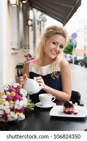 A beautiful woman are pouring tea. Holding a cup of tea. Outdoors