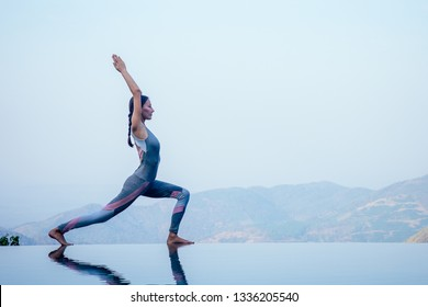 Beautiful woman practice yoga pose on the infinity pool above the mountain peak in the morning in front of beautiful nature views in india goa wildernest nature resorte .romance sunrise in mountains