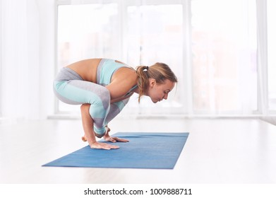 Beautiful woman practices handstand yoga asana Bhuja Pidasana - Arm pressure pose at the yoga studio