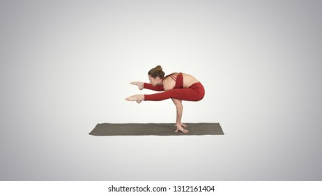 Beautiful woman practices handstand yoga asana Tittibhasana - firefly pose on gradient background.