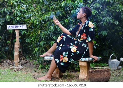 Beautiful woman practicing magic. Witch using sage and healing crystals in nature. Forest witch on a coffee farm in Puerto Rico. Hispanic woman outside with burning sage. Crystal healing, sage cleanse