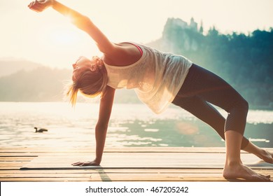 Beautiful woman practicing Yoga by the lake. Sunset. Toned image