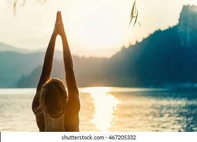 Beautiful woman practicing Yoga by the lake - Sun salutation series - Upward hands pose - Toned image