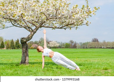 Beautiful woman is practicing yoga, doing Camatkarasana pose near blossom tree at the park.