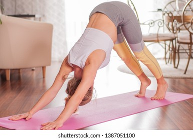 Beautiful woman is practicing yoga, doing Adho Mukha Svanasana pose, standing in Downward facing dog exercise at home