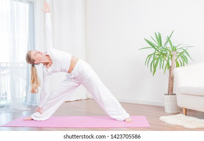 Beautiful woman is practicing yoga at home on yoga mat, girl doing Utthita Trikonasana exercise, extended triangle pose