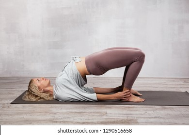 Beautiful woman practicing yoga in living room or in yoga class
