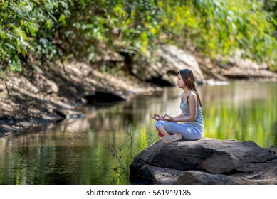 Beautiful woman practicing yoga on the rock in a stream.