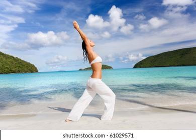 beautiful woman practicing yoga on beach