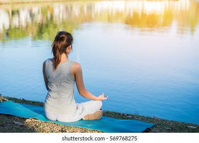 Beautiful woman practicing yoga waterfront in the park.