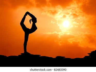 beautiful woman practise yoga at sunset silhouetted