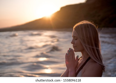 Beautiful woman prays on the sea shore on the sunset