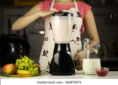 A beautiful woman preparing a milk cocktail with fruits in the kitchen.