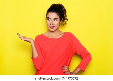 Beautiful woman presenting something with hand. Studio shot on yellow screen.