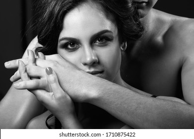A beautiful woman presses her face against a man's hands