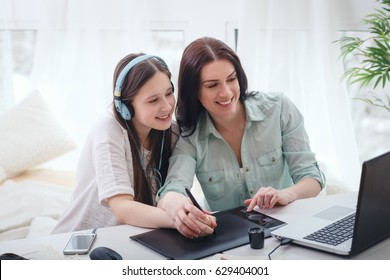 Beautiful woman and pretty teenager girl drawing illustrations together with digital tablet and stylus