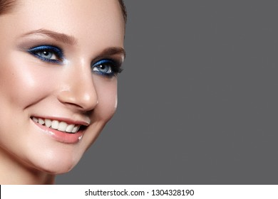 Beautiful Woman with Professional Blue Makeup. Celebrate Style Eye Make-up and Shine Skin. Smiling Fashion Model. Beautifil Happy Smile
