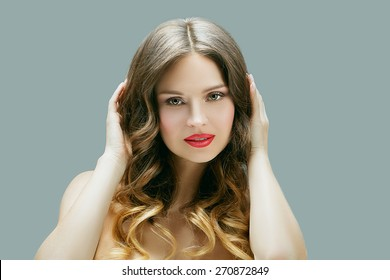 Beautiful woman with professional hair style and make up. Blond curly hair with ombre coloring, clean shiny skin.