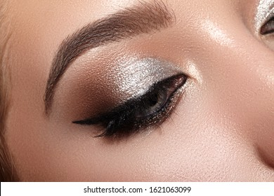 Beautiful Woman with Professional Makeup. Closeup Macro of Woman Face with Cat-Eye Make-up. Fashion Celebrate Makeup, Perfect Eyebrows, Glowy Clean Skin, perfect Shapes of Brows. Shiny Shimmer