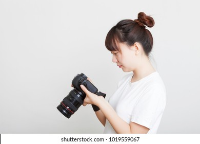 The beautiful woman is a professional photographer of the SLR camera