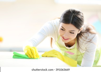 Beautiful woman in protective gloves cleaning kitchen table with rag