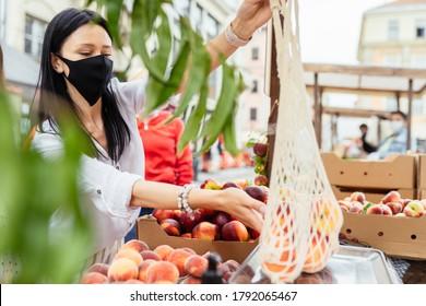 Schöne Frau in Schutzmasken ist die Wahl und das Wiegen von Bio-Pfirsichen auf dem Lebensmittelmarkt im Sommer. Wiederverwendbare Öko-Meshtasche zum Einkaufen. Konzept der Abfallvermeidung