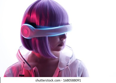 Beautiful woman with purple hair in futuristic costume over white background. Girl in glasses of virtual reality. Augmented reality game, future technology, AI concept. VR. Blue and violet neon light.