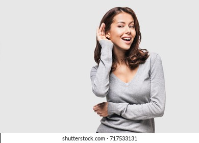 Beautiful woman puts a hand to the ear to hear better. Young girl listening something over white background