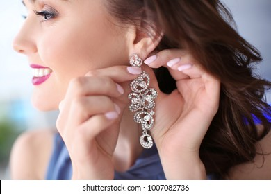 Beautiful woman putting on elegant earrings, closeup