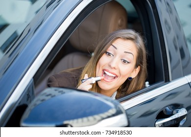 Beautiful woman putting on lipstick in car while looking at her self in the mirror