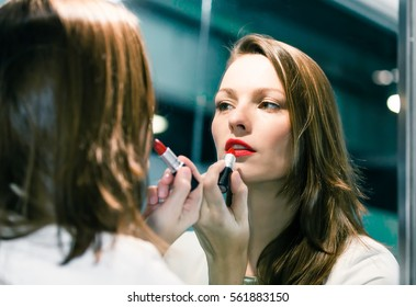 Beautiful woman putting on makeup in front of mirror