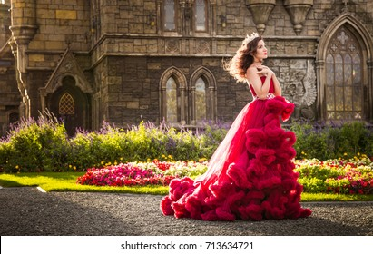 A beautiful woman, a queen in a burgundy lavish dress, walks along a flowering garden. Ancient, Gothic castle on the background. Copy space