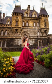 A beautiful woman, a queen in a burgundy lavish dress, walks along a flowering garden. Ancient castle on the background.