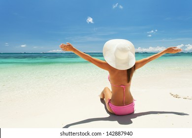 Beautiful woman raised her hands at the beach