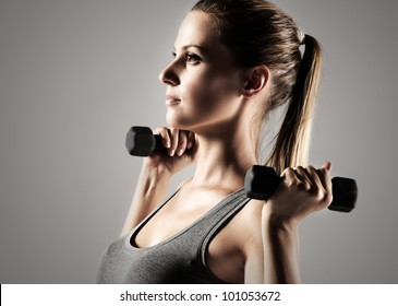 A beautiful woman raises with dumbbells
