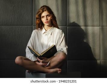 Schöne Frau liest Buch in einem Schlafzimmer