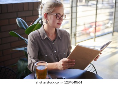 Beautiful woman reading book at cafe