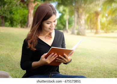Beautiful woman is reading a book in the garden.