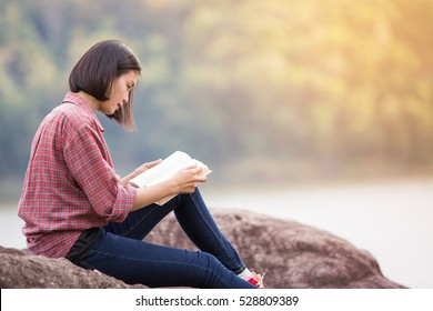beautiful woman reading a book in the nature