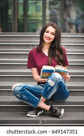 Beautiful woman reading a book on the steps of the building.