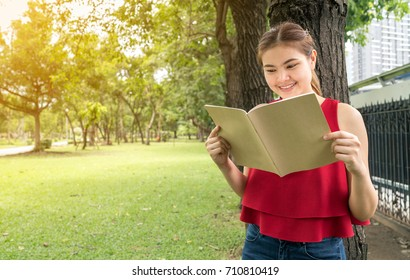 Beautiful woman reading a book in the park, she wears a red shirt, copy space.