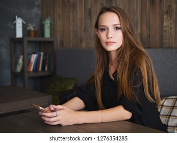 Beautiful woman reading good news on mobile phone during rest in coffee shop. Happy caucasian female watching photos on smartphone checking social networks while relaxing in cafe during free time