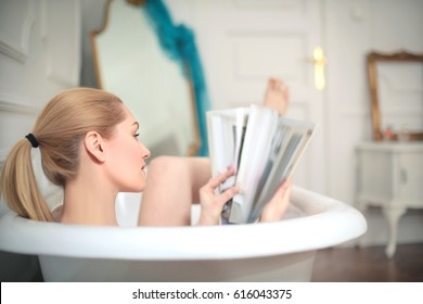Beautiful woman reading a magazine in the bathtub