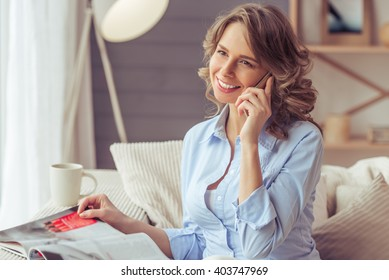 Beautiful woman is reading a magazine, talking on the mobile phone and smiling while sitting on sofa at home