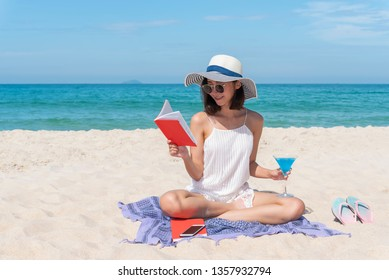 Beautiful woman reading on the tropical beach with relax in vacation. Summer travel concept.