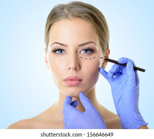 Beautiful woman ready for cosmetic surgery, female face with doctor's hands drawing lines on skin, over blue