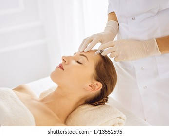 Beautiful woman receiving beauty injections with closed eyes. Beautician doctor hands doing beauty procedure to female face with syringe