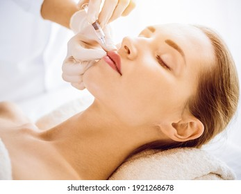 Beautiful woman receiving beauty injections with closed eyes in sunny medical center. Beautician doctor hands doing beauty procedure to female face with syringe. Cosmetic medicine and surgery concept