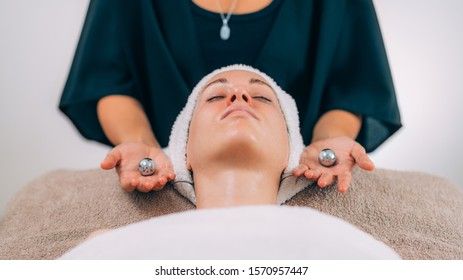 Beautiful woman receiving face lymphatic drainage treatment with Chinese meditation balls.